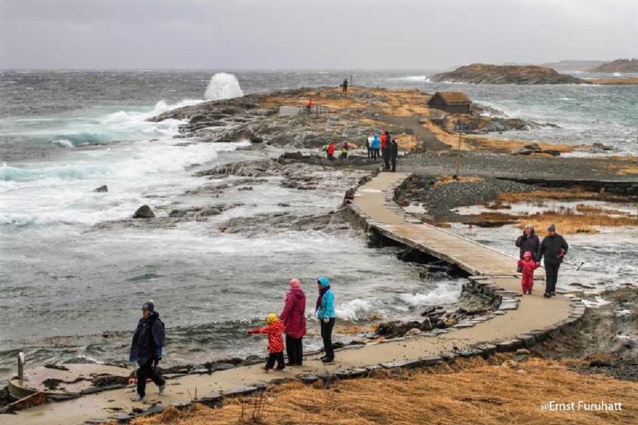Folk på stenbro ved havet